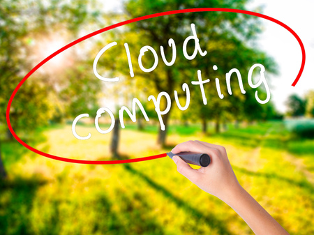 green computing: Woman Hand Writing Cloud computing on blank transparent board with a marker isolated over green field background. Business concept. Stock Photo