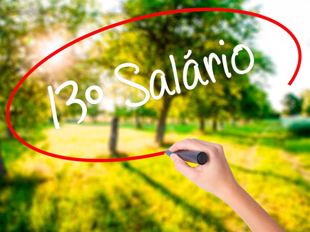 Woman Hand Writing 13 Salary (13o salario In Portuguese)  on blank transparent board with a marker isolated over green field background. Stock Photo
