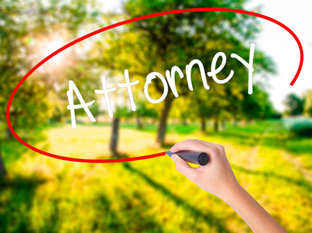 deeds: Woman Hand Writing Attorney  on blank transparent board with a marker isolated over green field background. Business concept. Stock Photo Stock Photo
