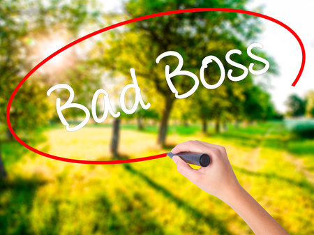 Woman Hand Writing Bad Boss on blank transparent board with a marker isolated over green field background. Stock Photo