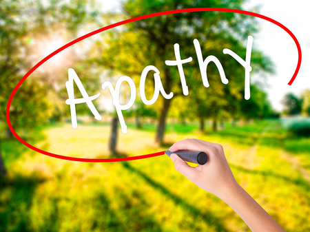 Woman Hand Writing Apathy  on blank transparent board with a marker isolated over green field background. Stock Photo