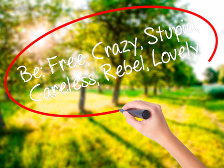 Woman Hand Writing Be: Free, Crazy, Stupid, Careless, Rebel, Lovely on blank transparent board with a marker isolated over green field background. Stock Photo