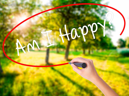 Woman Hand Writing Am I Happy? on blank transparent board with a marker isolated over green field background. Stock Photo