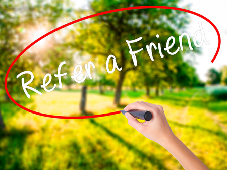 Woman Hand Writing Refer a Friend  on blank transparent board with a marker isolated over green field background. Business concept. Stock Photo