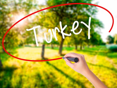 Woman Hand Writing Turkey  on blank transparent board with a marker isolated over green field background. Business concept. Stock Photo Stock Photo