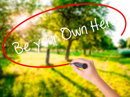 Woman Hand Writing  Be your Own Hero  on blank transparent board with a marker isolated over green field background. Business concept. Stock Photo