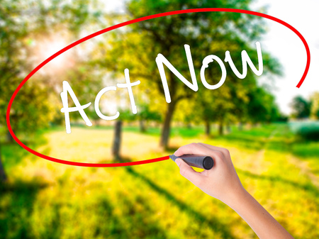 Woman Hand Writing Act Now on blank transparent board with a marker isolated over green field background. Stock Photo Stock Photo