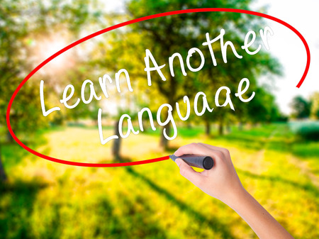 Woman Hand Writing Learn Another Language with a marker over transparent board . Isolated on green field. Learn, technology, internet concept. Stock Image