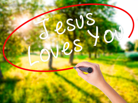testament schreiben: Woman Hand Writing Jesus Loves You with a marker over transparent board . Isolated on green field. Religion, technology, internet concept. Stock Image