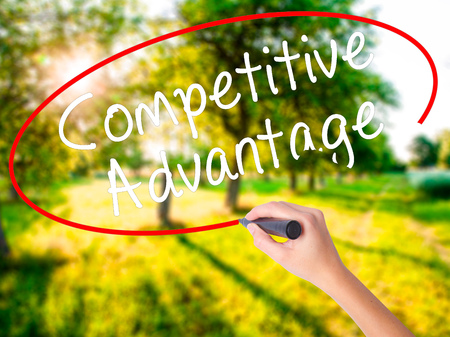 Woman Hand Writing Competitive Advantage on blank transparent board with a marker isolated over green field background. Business concept. Stock Photo