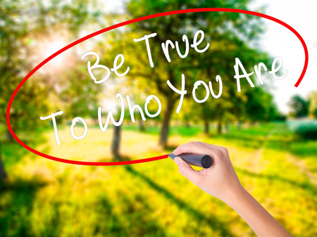 Woman Hand Writing Be True To Who You Are on blank transparent board with a marker isolated over green field background. Business concept. Stock Photo