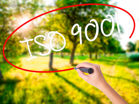Woman Hand Writing  Iso 9001 on blank transparent board with a marker isolated over green field background. Business concept. Stock Photo