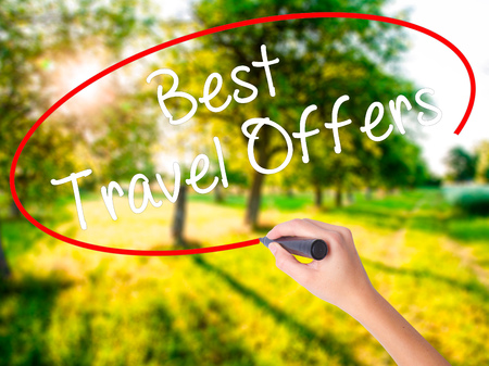 Woman Hand Writing Best Travel Offers  with a marker over transparent board . Isolated on green field. Travel technology, internet concept. Stock Image