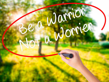 Woman Hand Writing Be a Warrior Not a Worrier on blank transparent board with a marker isolated over green field background. Stock Photo