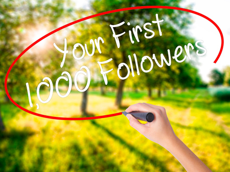 Woman Hand Writing Your First 1,000 Followers  on blank transparent board with a marker isolated over green field background. Business concept. Stock Photo