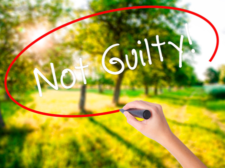 Woman Hand Writing NOT GUILTY on blank transparent board with a marker isolated over green field background. Business concept. Stock Photo Stock Photo