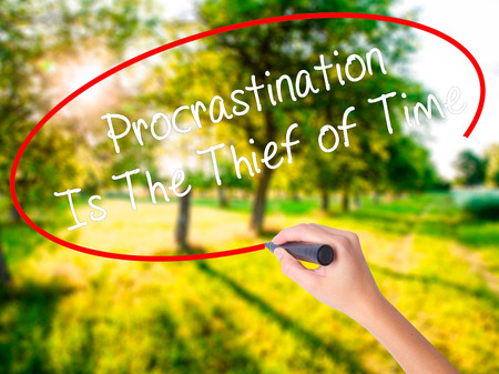 Woman Hand Writing  Procrastination Is The Thief of Time on blank transparent board with a marker isolated over green field background. Business concept. Stock Photo Stock Photo