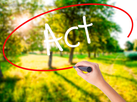 Woman Hand Writing Act  on blank transparent board with a marker isolated over green field background. Stock Photo