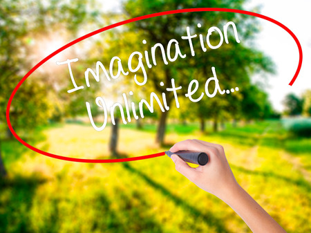 Woman Hand Writing Imagination Unlimited... on blank transparent board with a marker isolated over green field background. Business concept. Stock Photo