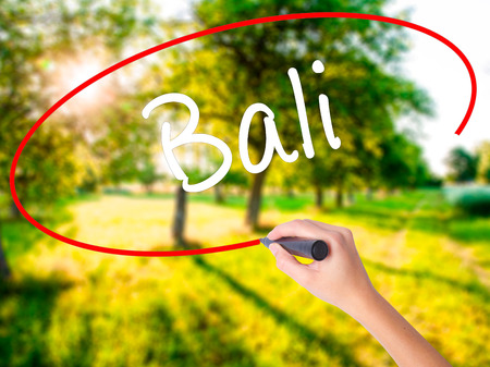 bali province: Woman Hand Writing Bali  on blank transparent board with a marker isolated over green field background. Business concept. Stock Photo Stock Photo