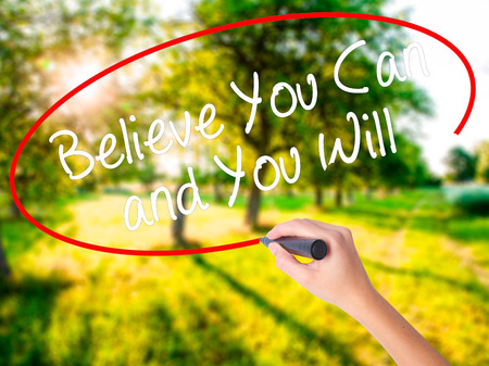 tu puedes: Woman Hand Writing Believe You Can and You Will on blank transparent board with a marker isolated over green field background. Business concept. Stock Photo