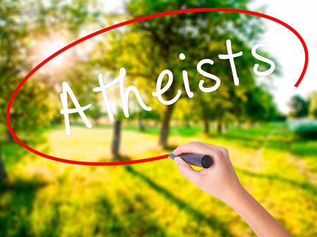 disbelieve: Woman Hand Writing Atheists on blank transparent board with a marker isolated over green field background. Business concept. Stock Photo