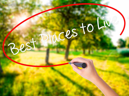 Woman Hand Writing Best Places to Live on blank transparent board with a marker isolated over green field background. Stock Photo Stock Photo