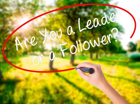 blindly: Woman Hand Writing Are You a Leader or a Follower? on blank transparent board with a marker isolated over green field background. Business concept. Stock Photo