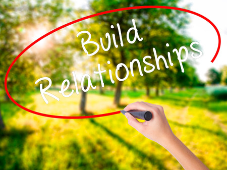 Woman Hand Writing Build Relationships on blank transparent board with a marker isolated over green field background. Business concept. Stock Photo