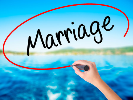 Woman Hand Writing Marriage on blank transparent board with a marker isolated over water background. Business concept. Stock Photo