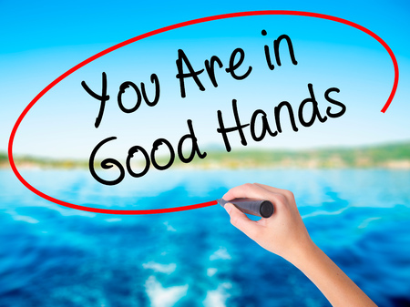 Woman Hand Writing You Are in Good Hands on blank transparent board with a marker isolated over water background. Business concept. Stock Photo