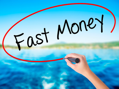 Woman Hand Writing Fast Money  on blank transparent board with a marker isolated over water background. Business concept. Stock Photo