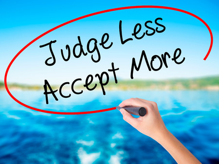 Woman Hand Writing Judge Less Accept More on blank transparent board with a marker isolated over water background. Business concept. Stock Photo Stock Photo