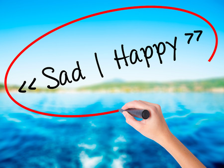 Woman Hand Writing Sad - Happy on blank transparent board with a marker isolated over water background. Business concept. Stock Photo Stock Photo
