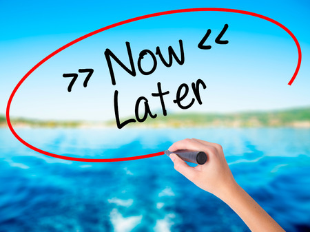 Woman Hand Writing NowLater on blank transparent board with a marker isolated over water background. Business concept. Stock Photo