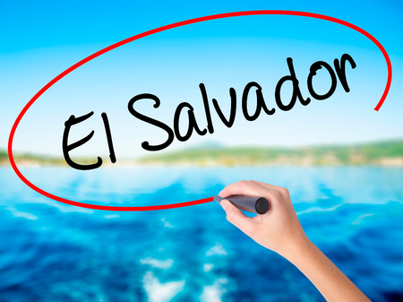 Woman Hand Writing El Salvador on blank transparent board with a marker isolated over water background. Business concept. Stock Photo