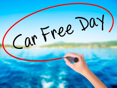 Woman Hand Writing Car Free Day on blank transparent board with a marker isolated over water background. Business concept. Stock Photo Stock Photo