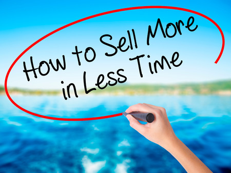 work less: Woman Hand Writing How to Sell More in Less Time on blank transparent board with a marker isolated over water background. Business concept. Stock Photo
