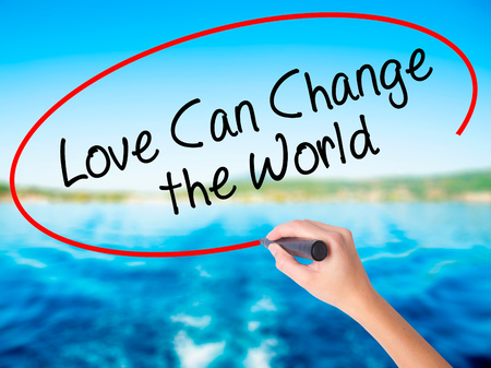 Woman Hand Writing Love Can Change the World on blank transparent board with a marker isolated over water background. Business concept. Stock Photo Stock Photo