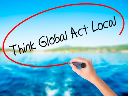 Woman Hand Writing Think Global Act Local on blank transparent board with a marker isolated over water background. Business concept. Stock Photo