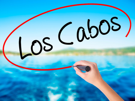 Woman Hand Writing Los Cabos on blank transparent board with a marker isolated over water background. Business concept. Stock Photo