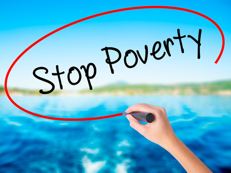 eradication: Woman Hand Writing Stop Poverty  on blank transparent board with a marker isolated over water background. Business concept. Stock Photo