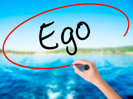 Woman Hand Writing Ego on blank transparent board with a marker isolated over water background. Business concept. Stock Photo Stock Photo
