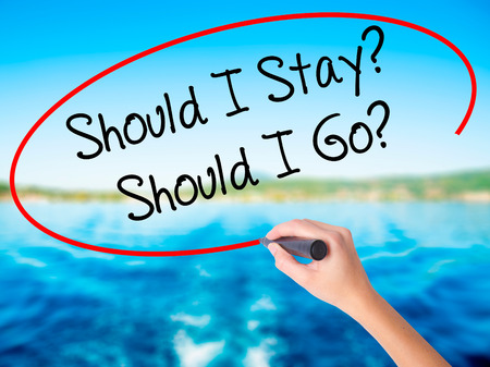 indecisiveness: Woman Hand Writing Should I Stay? Should I Go? on blank transparent board with a marker isolated over water background. Business concept. Stock Photo