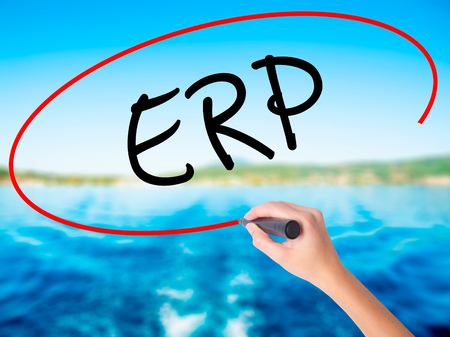 Woman Hand Writing  ERP (Enterprise Resource Planning)   on blank transparent board with a marker isolated over water background. Business concept. Stock Photo
