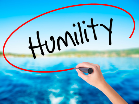 humility: Woman Hand Writing Humility  on blank transparent board with a marker isolated over water background. Business concept. Stock Photo