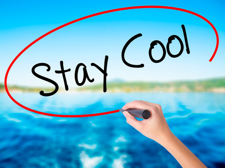 hassle: Woman Hand Writing Stay Cool   on blank transparent board with a marker isolated over water background. Business concept. Stock Photo