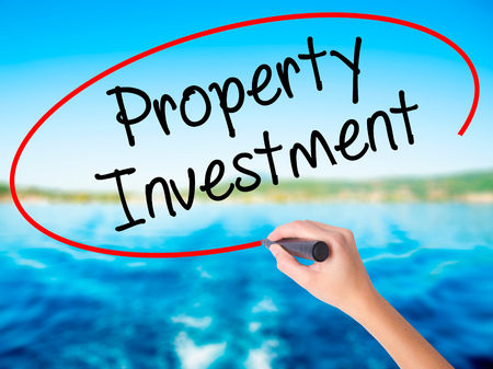 Woman Hand Writing Property Investment on blank transparent board with a marker isolated over water background. Business concept. Stock Photo