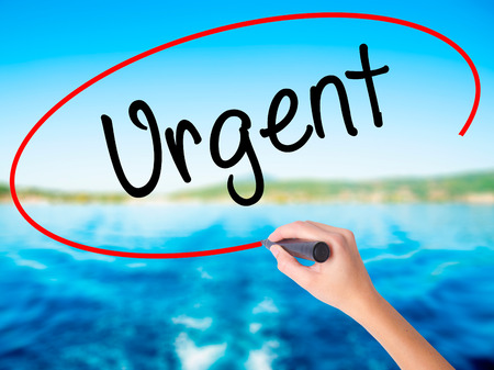 Woman Hand Writing Urgent  with a marker over transparent board. Isolated on background. Business, technology, internet concept. Stock  Photo