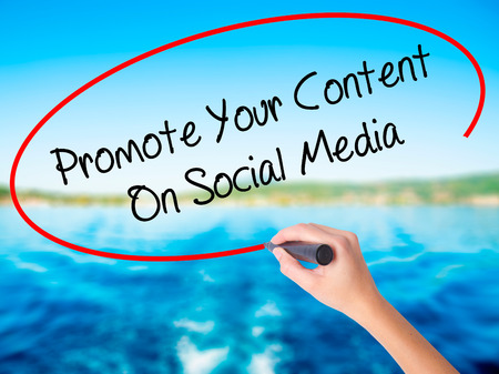 Woman Hand Writing Promote Your Content On Social Media  on blank transparent board with a marker isolated over water background. Business concept. Stock Photo